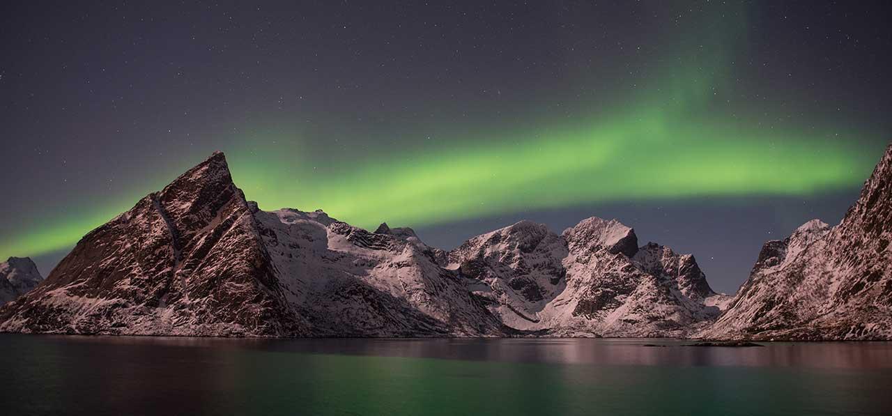 Grønt nordlys bak bratte snødekte fell som kommer opp av et vann som reflekterer fargen av norlyset.