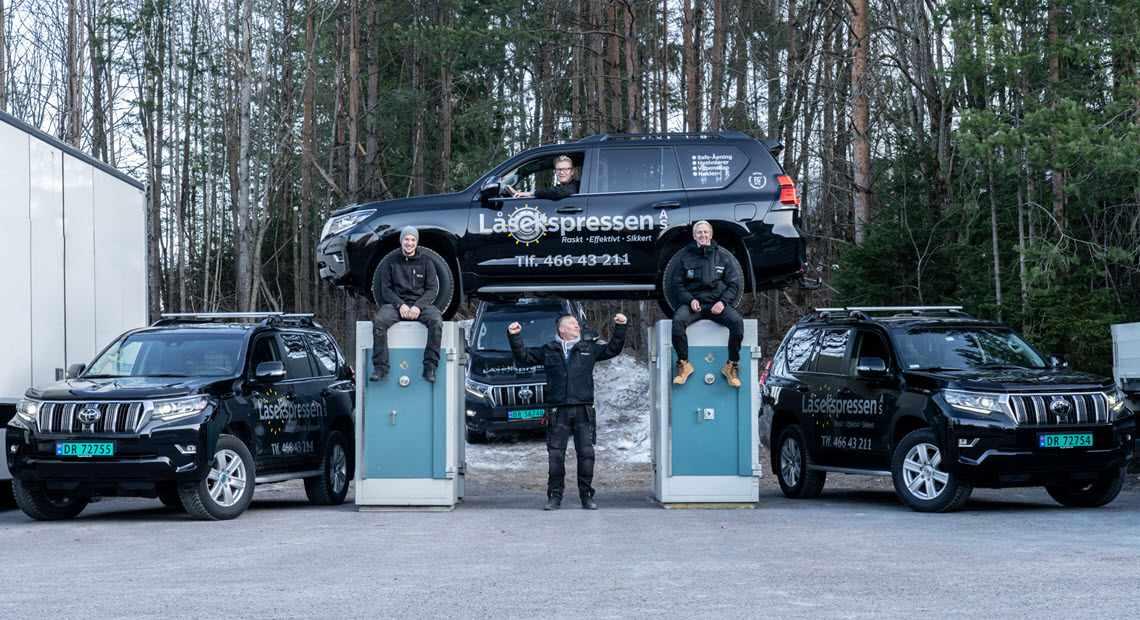 låsekspressen-teamet foran to store safer med en firmabil plassert oppå.